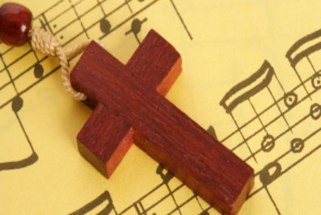 Closeup of wooden crucifix on yellow music sheet